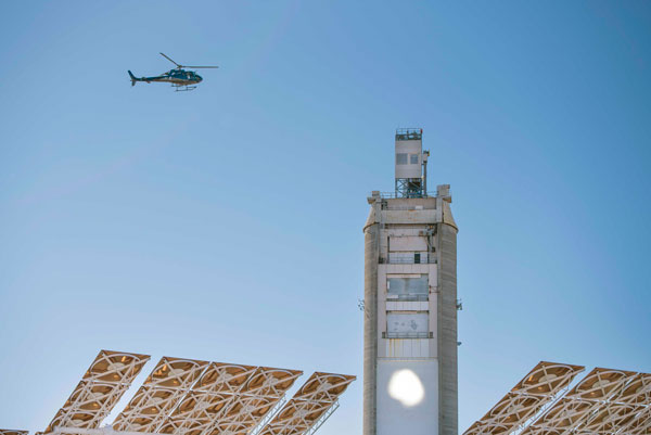 helicopter flies over solar tower