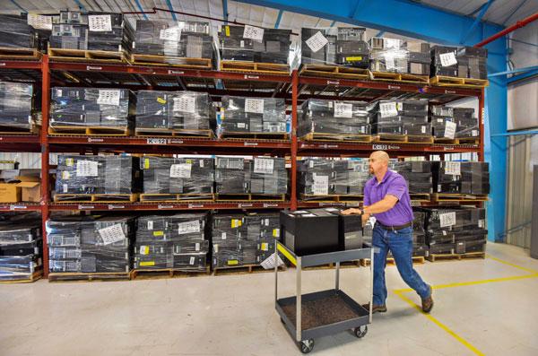 Michael Somuk wheels cart through computer warehouse