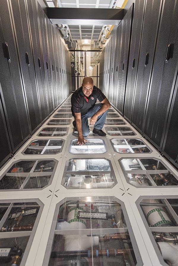 Sandia engineer David J. Martinez examines the cooling system at Sandia's supercomputing center.  Photo by Randy Montoya
