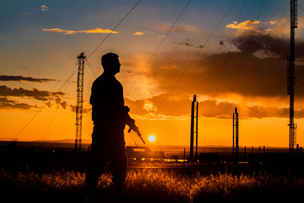 officer silhouetted against sunset