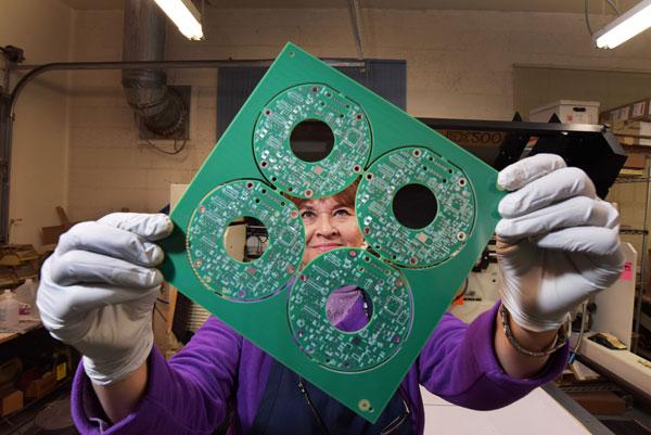 Judy Ortiz Rizek holds a printed circuit board