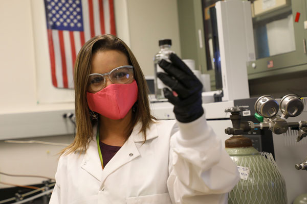 Jessica Kruichak holding a sample vial in the lab