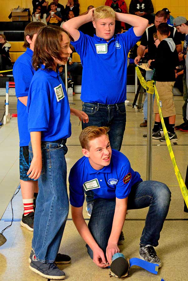 Students check their team standings after racing their electric car.