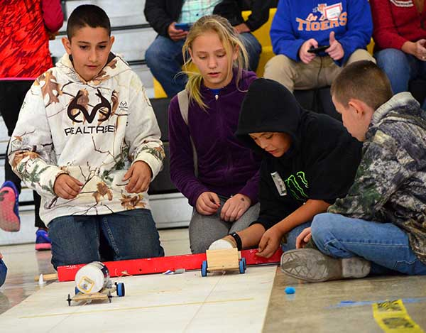 Students watch as their electric cars race down the practice track during the New Mexico Electric Car Challenge.