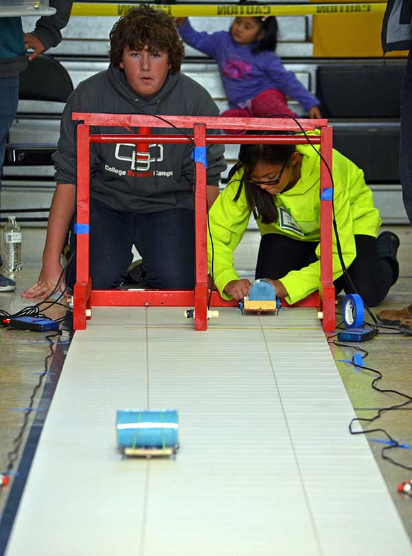 """Two students watch as their electric cars race down a 10-meter track during the New Mexico Electric Car Challenge. More than 150 middle school students from across New Mexico participated in the challenge, presented by Sandia National Laboratories, Los Alamos National Laboratory, PNM and Intel. The challenge, held Nov. 19 at Albuquerque's Van Buren Middle School, is an annual STEM event in its 10th year. Students formed 5-person teams at the beginning of the school year and were provided basic materials—a lithium-ion battery, a direct-current motor, and other materials such as a chassis and wheels—needed to build their cars.""""Our goal is to expose students to basic engineering. This allows them to see how math and science intersect,"""" said Amy Tapia, Sandia's community relations manager.The teams were also required to give oral presentations on the designs of their cars, as well as the challenges they faced while constructing and running them."""