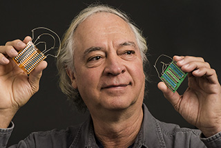 RESEARCHER JUAN ELIZONDO-DECANINI (2624) holds two compact, high-voltage nonlinear transmission lines. Juan leads a project on nonlinear behavior in materials — behavior that's usually shunned because it's so unpredictable.