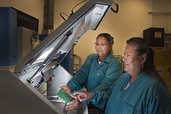 LAB EXPANSION — Maxine Norton, left, and Etta Tsosie (both 5346) work on electronics in a newly expanded section of the Light Electrical Lab. The now-completed upgrade doubled the lab's floor space, making room for new equipment to take their work to the next level. The lab serves all Sandians.(Photo by Randy Montoya)