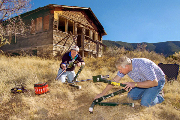 Rod Owenby and Chris Cherry use equipment on ground outside abandoned cabin