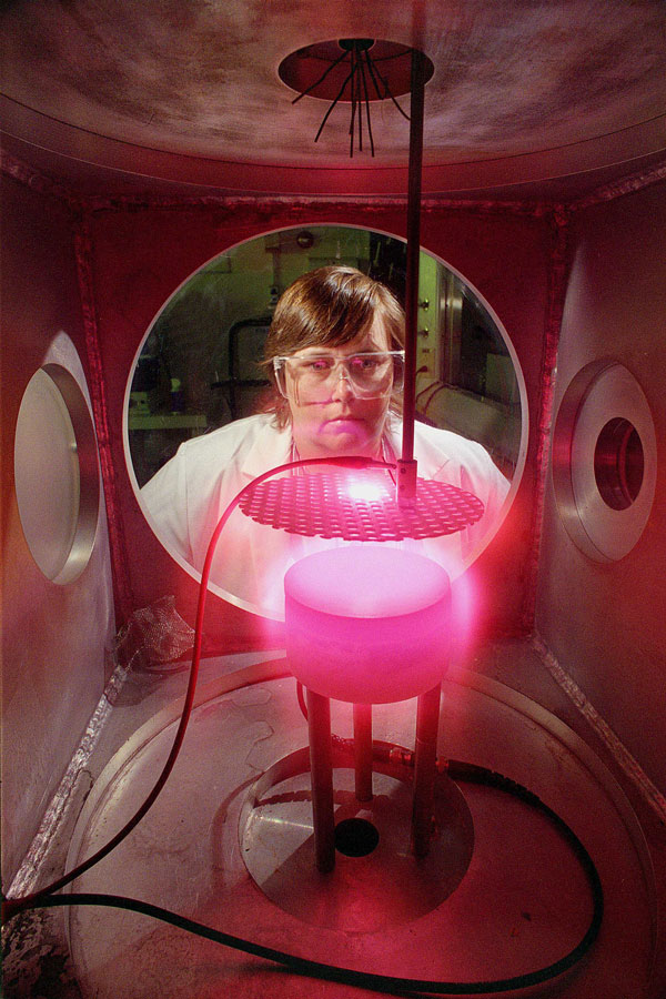 Pam Ward in lab gear looks at glowing pink plasma in case