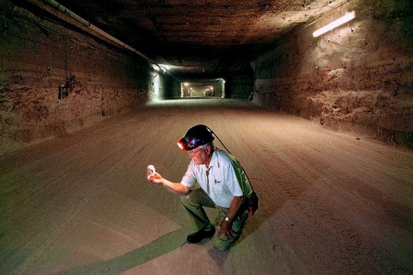 Wendell Weart in hard hat kneels in giant underground tunnel