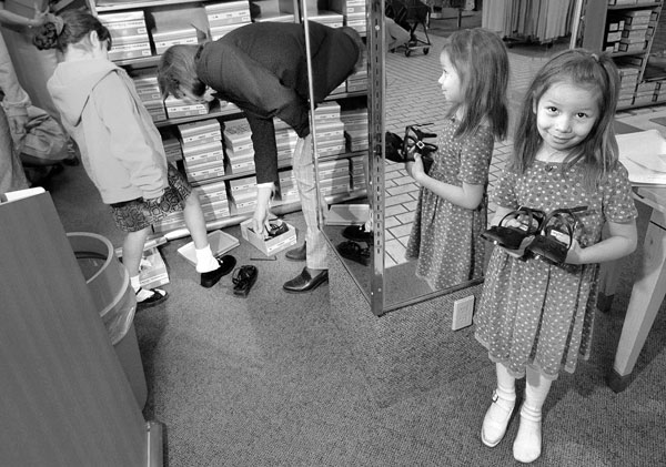 child in shoe store holds pair of shoes
