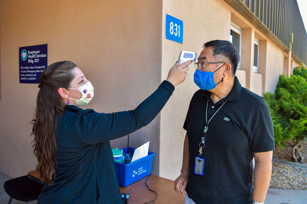 medical worker conducts on-site health check for employee