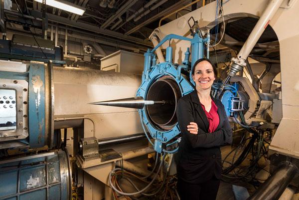 Katya Casper poses in front of wind tunnel
