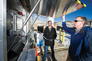 Mechanical engineer Terry Johnson, left, the project leader for the Hydrogen Station Equipment Performance (HyStEP) device, and National Renewable Energy Laboratory researcher Chris Ainscough prepare HyStEP for testing at NREL's Energy Systems Integration Lab. HyStEP will accelerate hydrogen refueling station commissioning.(Photo by Dennis Schroeder/NREL)