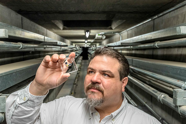 scientist holds up micro sensor