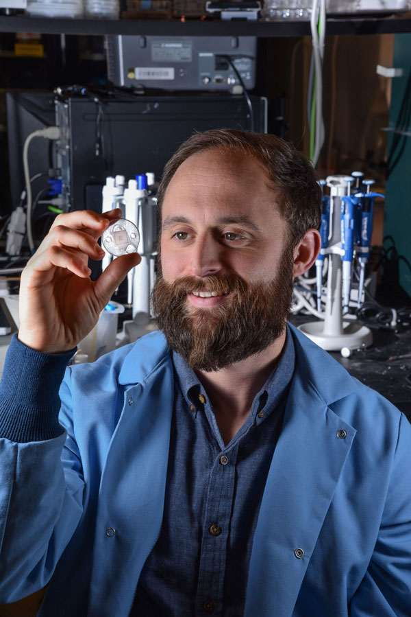 Philip Miller examines a microneedle device