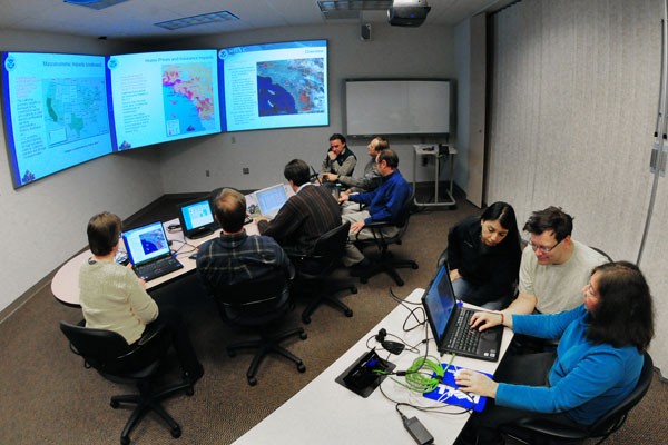 people in conference room looking at data on monitors