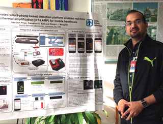 WINNING POSTER — Aashish Priye shows his winning poster in the annual Postdoctoral Technical Showcase at Sandia California. The showcase is held each December at Sandia's campuses in New Mexico and California to display the breadth of research by postdoctoral employees. (Photo by Jasmine King-Bush)