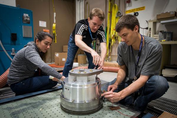 scientists work on vibration test equipment