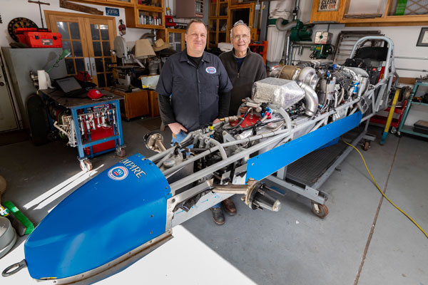 Joel and Jack Wirth work on roadster in garage