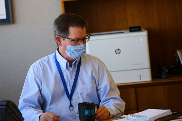 Labs Director working at desk wearing face masks