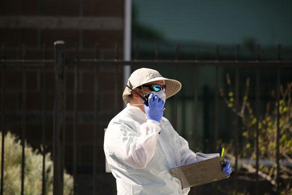 employee outside medical clinic in PPE talking on walkie talkie