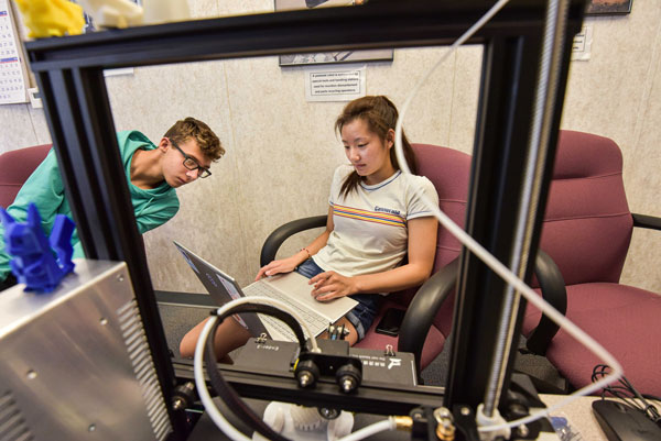 Students collaborate over laptop