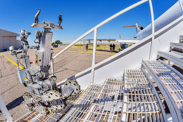 A robot climbs stairs to the cabin of a cargo plane