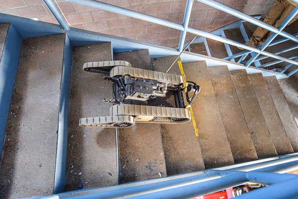 A robot maneuvers down stairs