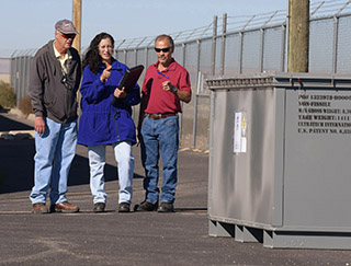 HOWARD SEELEY, left, Linda Gonzales, and Leroy Duran (all 4144), review a recent shipment ofwaste items bound for the Nevada National Security Site (NNSS). The three are members ofSandia's Waste Management and Pollution Prevention team, which this summer wrapped up aproject with the United States Air Force to transfer excess nuclear materials from a site inAlaska to the NNSS. (Photo by Randy Montoya)