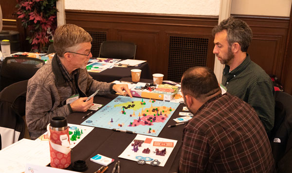 group of players examine game board