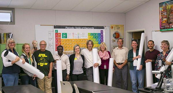 Livermore High School science teachers pose with Sandia Community Relations Officer Madeline Burchard (center), holding their new classroom tables.