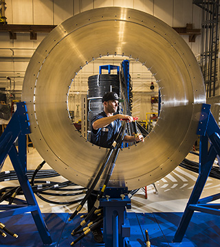 Caption: MAKING READY FOR THOR — Sandia tech Eric Breden (1651) terminates a transmission cable for installation on the silver disk that is the new pulsed-power machine's central powerflow assembly.(Photo by Randy Montoya)