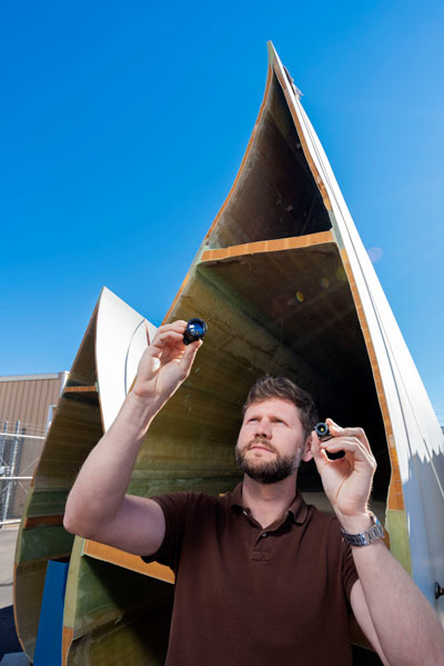 engineer inspects small camera in front of wind turbine