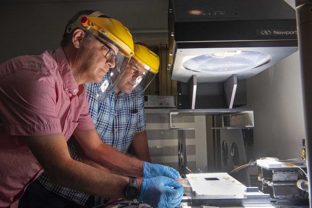 Joshua Stein, a Sandia systems engineer and director of the new Perovskite Photovoltaic Accelerator for Commercializing Technologies Center, left, prepares a solar module for testing at the Labs' Photovoltaic Systems Evaluation Laboratory, which will be used to support the commercialization of U.S. perovskite-based photovoltaic technologies.
