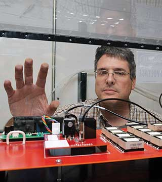 BOB KAPLAR (1768) peers at a test circuit built under a Grand Challenge Laboratory Directed Research and Development project to evaluate the switching performance of wide bandgap and ultra-wide bandgap power semiconductor devices.(Photo by Randy Montoya)