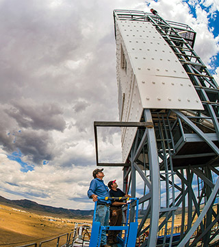 Technologists John Kelton and Daniel Ray inspect the Falling Particle Receiver during a cloud delay atop the National Solar Thermal Test Facility at Sandia National Laboratories.(Photo by Randy Montoya)
