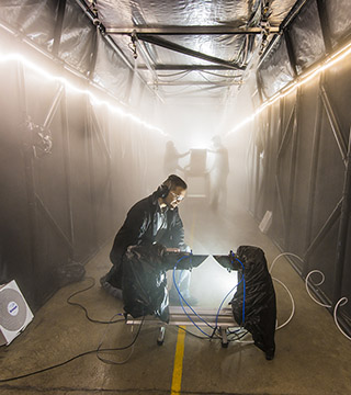 Andres Sanchez (6633) checks an instrument that measures the particle size and concentration in the atmosphere inside one of the world's largest fog chambers developed by Sandia.(Photo by Randy Montoya)