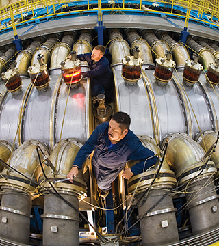 Former contractor JJ Montoya (foreground) and Chris Kirtley (1342) work atop the HERMES III Accelerator, making final adjustments on a newly rebuilt cavity.  (Photo by Randy Montoya)