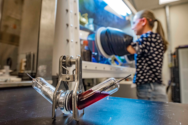 Researcher Martha Gross works in an argon glovebox with a test battery cell